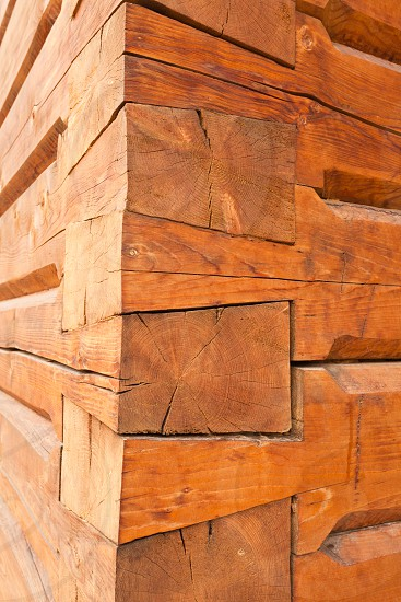 Sophisticated construction of joints of wooden timber logs meeting at the corner of log house photo