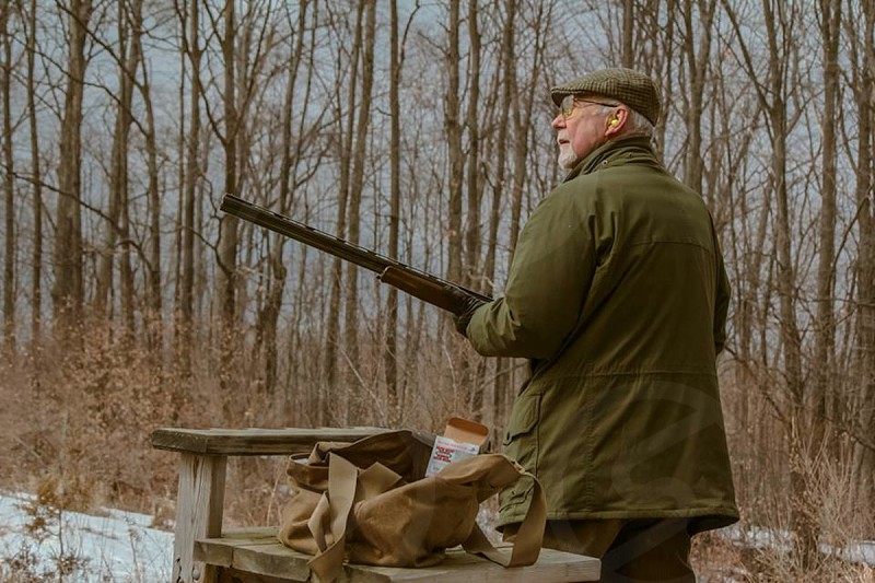 man in olive coat and newsboy cap with hunting rifle near table in woods photo
