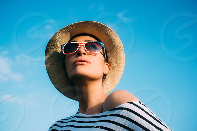 Close up Fashionable Young Woman in Beach Attire. Head and Shoulder Shot of a Fashionable Young Woman in Beach Hat and Sunglasses Looking Into the Distance Against Light Blue Sky Background. photo