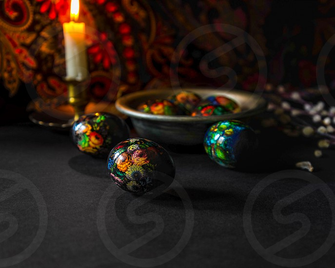 Easter eggs and a candle on a dark background photo