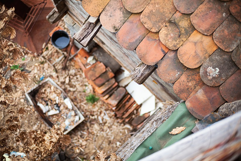 View from an old roof on tiles and backyard garden full of old things in blur. Village lifestyle details.  photo
