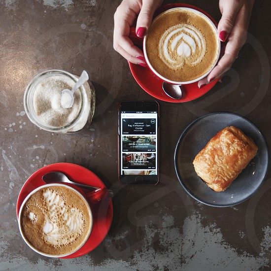 two foam espressos pastry and sugar in a bowl surrounding a smartphone photo
