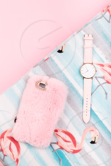 Mobile phone in pink case watch with pink stripe on pink background photo