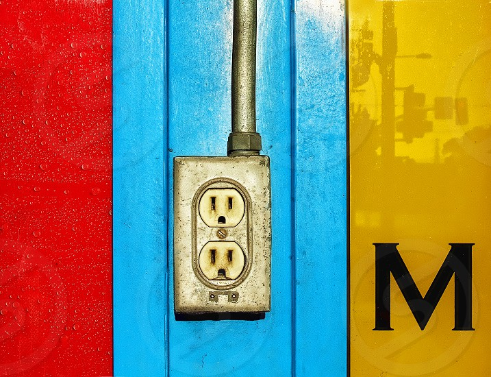 Detail of a wall with primary colors: redblue and yellow an electrical outlet and letter 'M.' photo