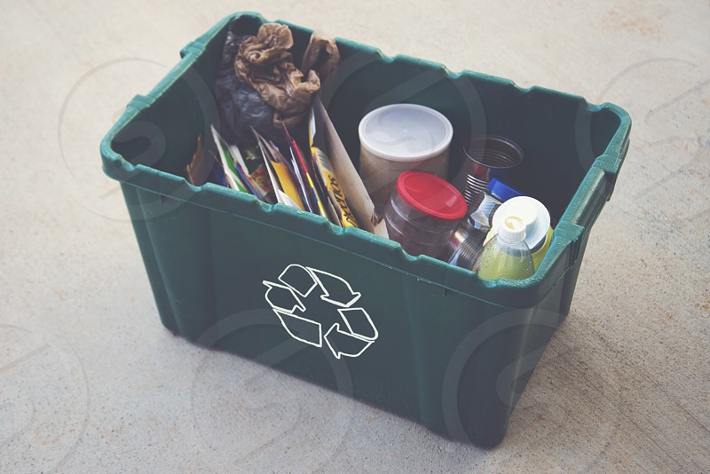 cans and bottles in green recyclable container photo
