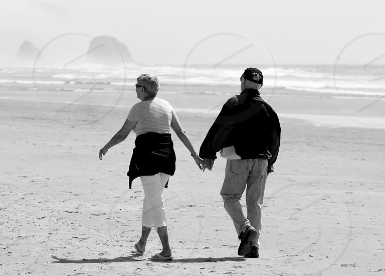 Older Man and Woman Walking Beach photo