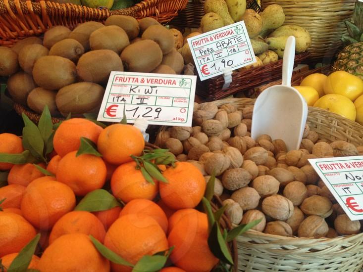 bundle of orange fruit on brown wicker basket beside nuts close up photography photo