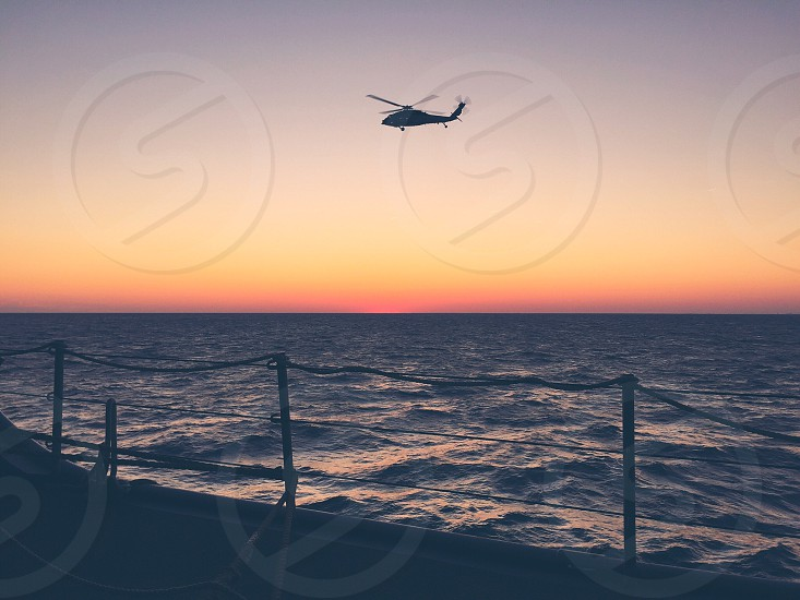 Sea helicopter golden hour ship water ocean sunset glow helo navy photo