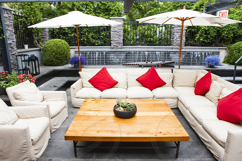 white fabric sectional sofa with red throw pillows on top and parasol behind photo