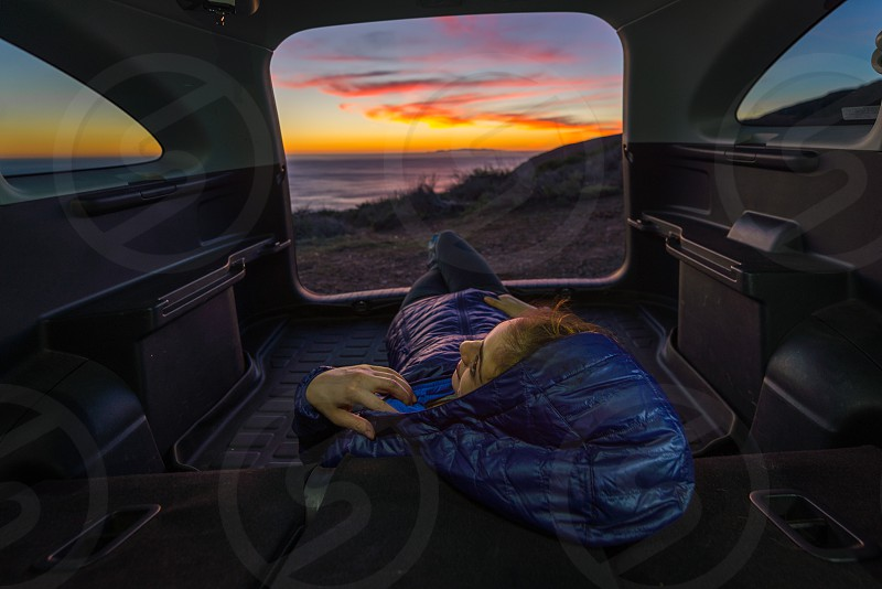 person in a blue blanket looking toward sunset photo