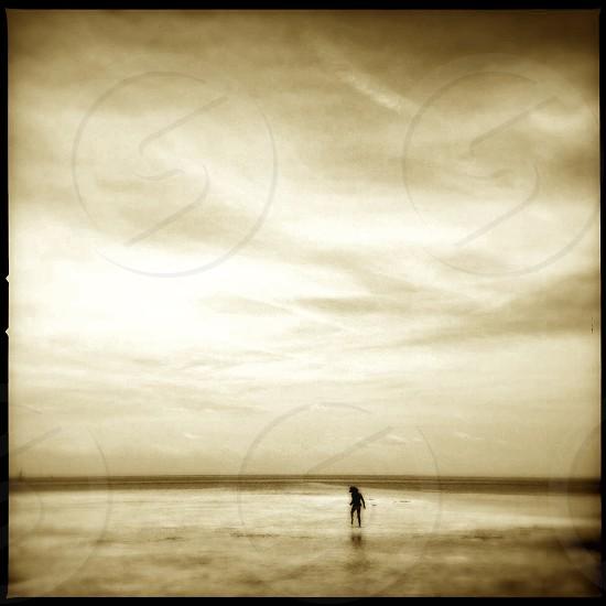 little girl exploring in a sandbar / sepia toned image photo