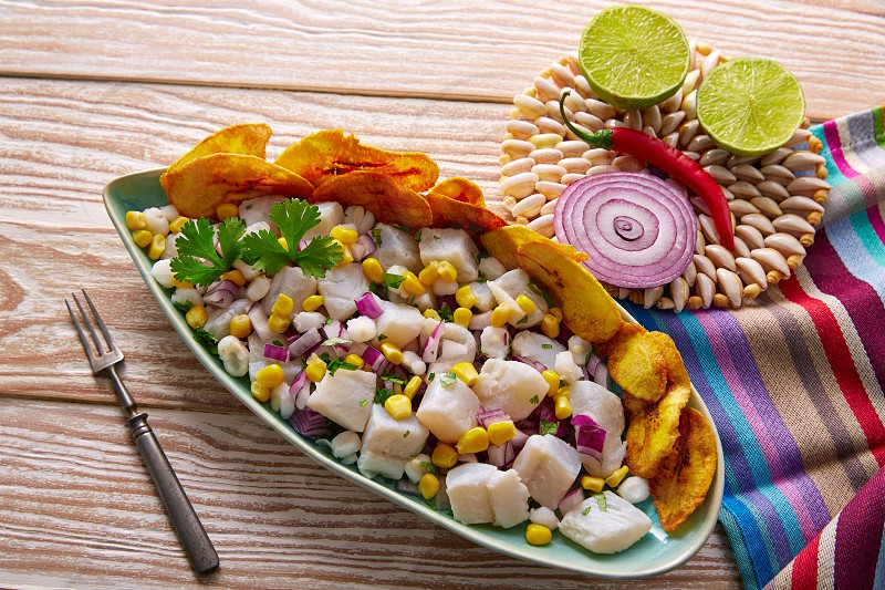 Ceviche peruvian recipe with fried banana and ingredients on wooden table photo