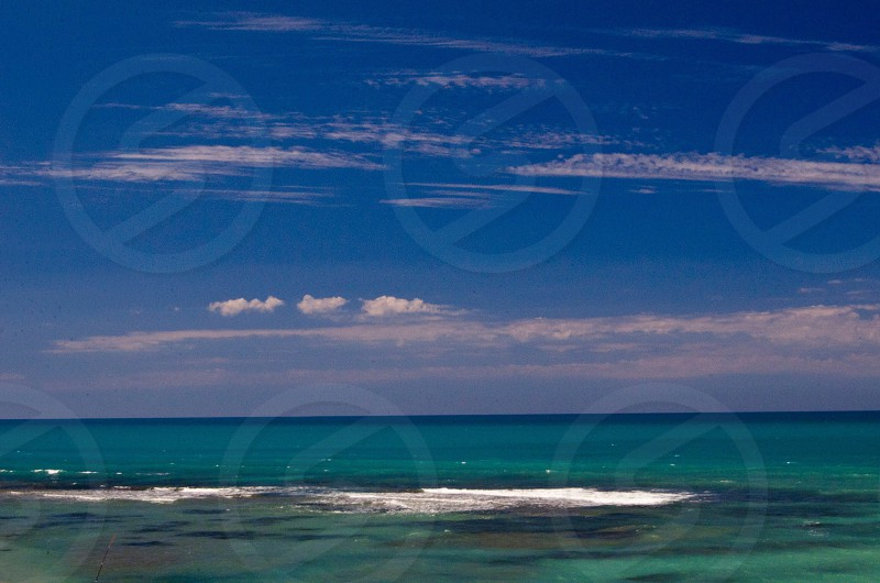 ocean water under blue sky and white clouds photo