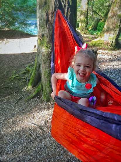 girl in green ruffle cap sleeve shirt in red and blue hammock tied on tree near body of water during daytime photo