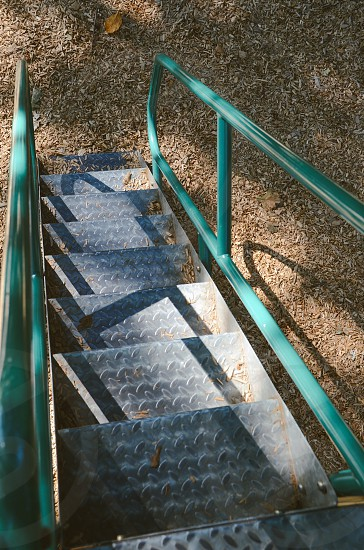 gray metal staircase with green stair railings photo