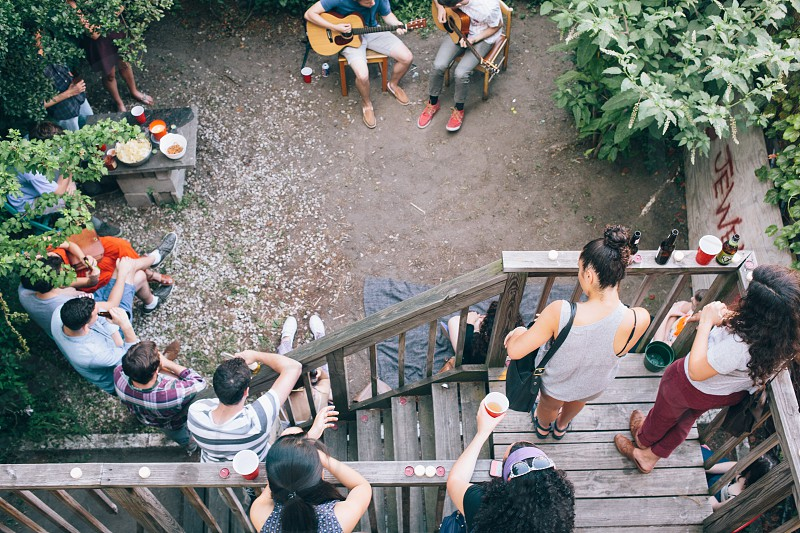 people on staircase watching 2 people playing guitar photo