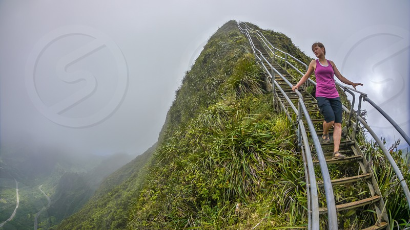 woman in pink tank top on brown and gray steel bridge beside green mountain under fog photo