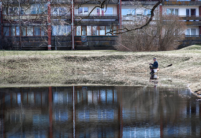 A man fishing in a pond of the city center photo