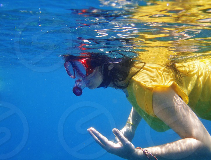 woman in yellow shirt wearing swimming goggles swimming underwater photography photo
