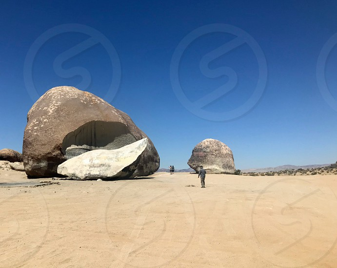 Seen in the distance a man walks over the desert sand to a huge boulder photo