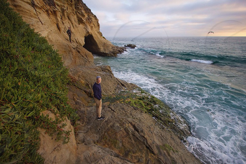 man in black and khakis on rock coast photo