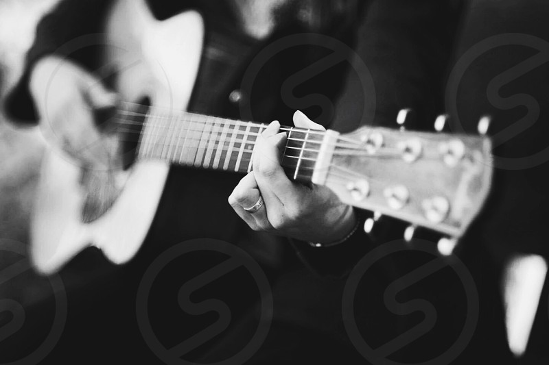 person playing acoustic guitar photo