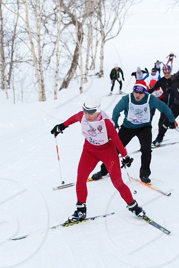 PETROPAVLOVSK CITY KAMCHATKA PENINSULA RUSSIAN FAR EAST - FEBRUARY 10 2018: Skiers running on ski track in winter forest. All-Russia mass ski race - Ski Track of Russia. photo