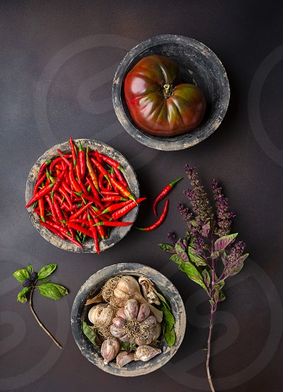 Overhead view of three rustic bowls of tomato chili peppers garlic and purple basil photo