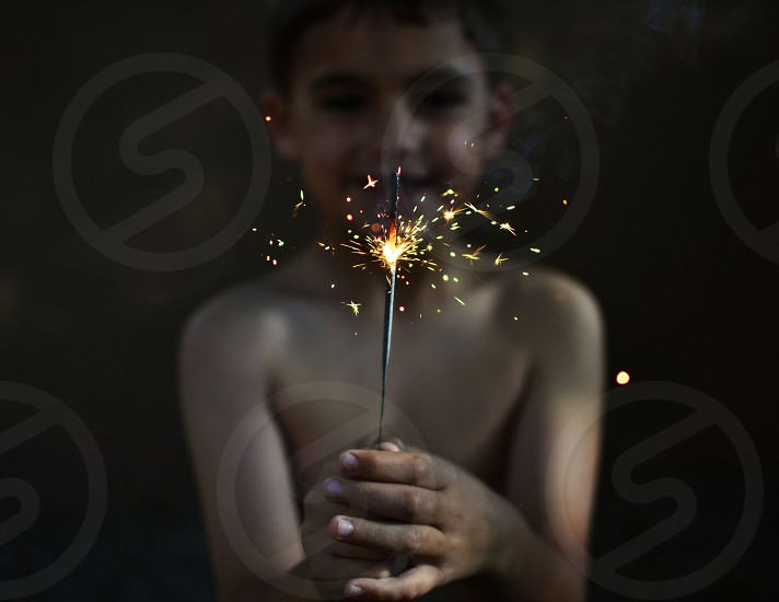 boy topless holding firecracker and smiling photo