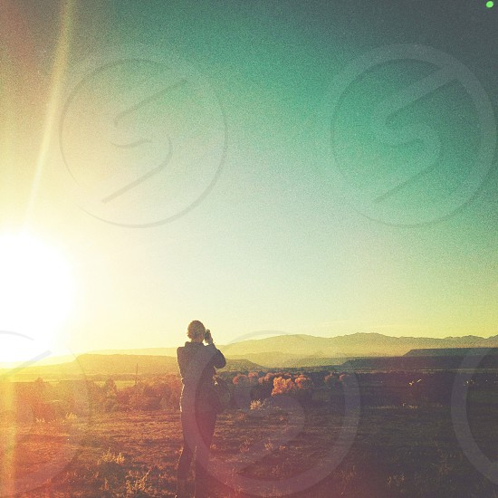 woman standing under sunrise view photo