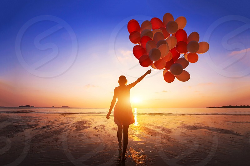 inspiration joy and happiness concept silhouette of woman with many flying balloons on the beach photo