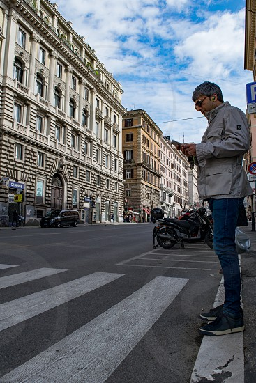 An adult male dressed in casual clothes with headphones in his ears standing on a pedestrian crosswalk looking down at his phone in a narrow street of Rome Italy photo