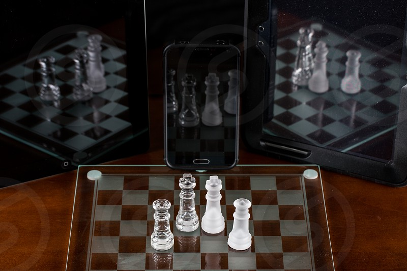 frosted and clear glass chess pieces on glass board reflected in black smartphone and tablet screens photo