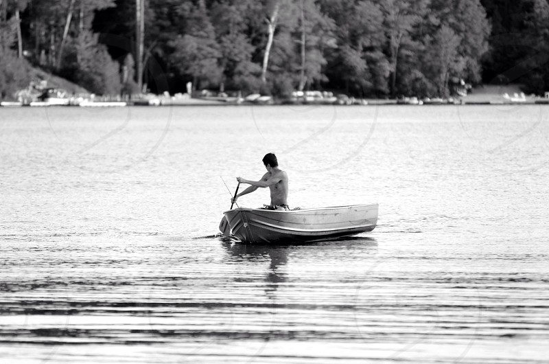grayscale photo of a man paddling on a boat on body of water during daytime photo