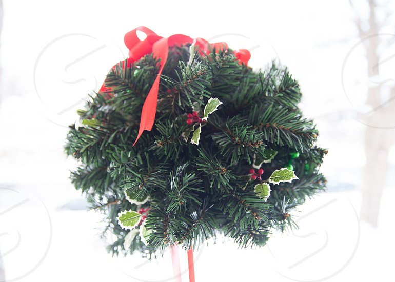 holly ball holly Christmas red ribbon snow ribbon red bow holly leaves pine pine needles Christmas decoration snowy day photo