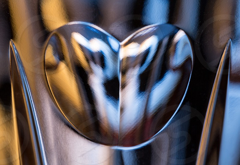 Detail of a cut glass champagne goblet with a heart on the side and reflecting lights from background photo