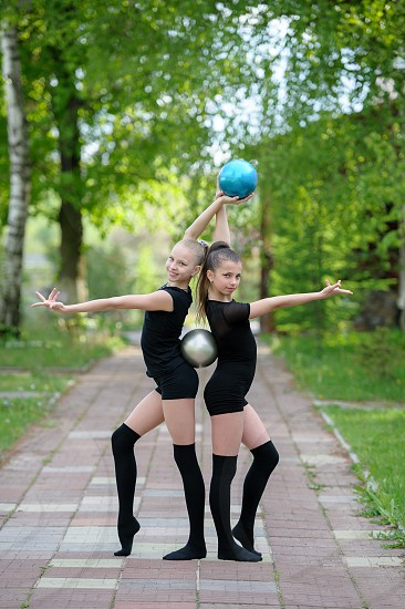 Two graceful gymnast girls posing with balls which are held with their hands and backs. Outdoor shot on bright summer day photo