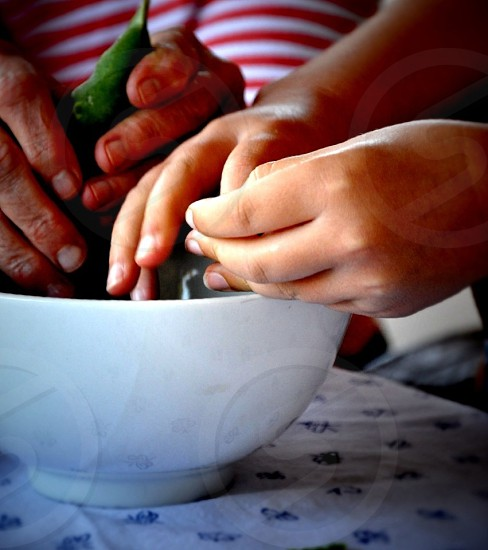 person's hands and white ceramic bowl photo