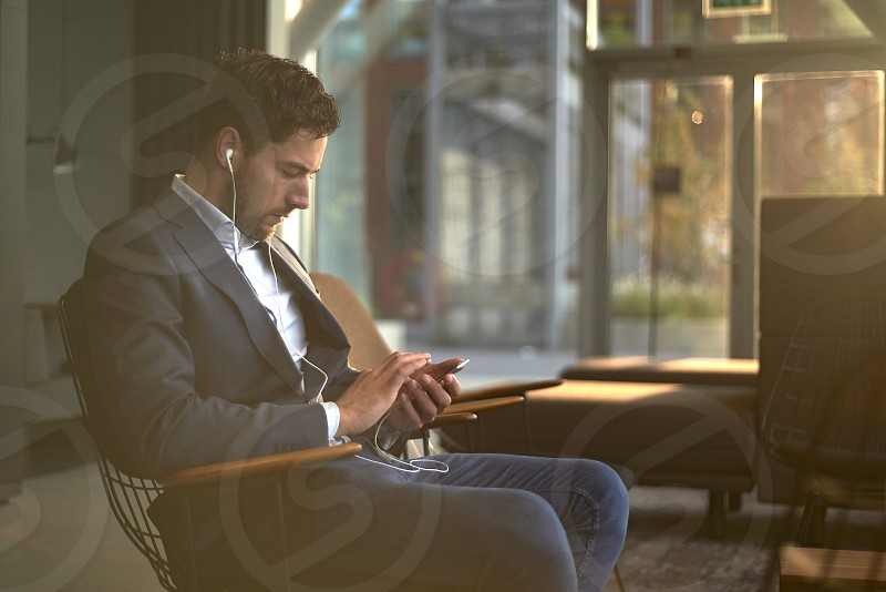Side profile of a business man sitting in a reception area of an office texting on his mobile phone with early morning sunlight coming in photo