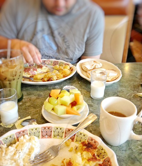 person eating scrambled eggs beside mash potatoes and omelet near coffee with milk and fresh sliced fruits photo