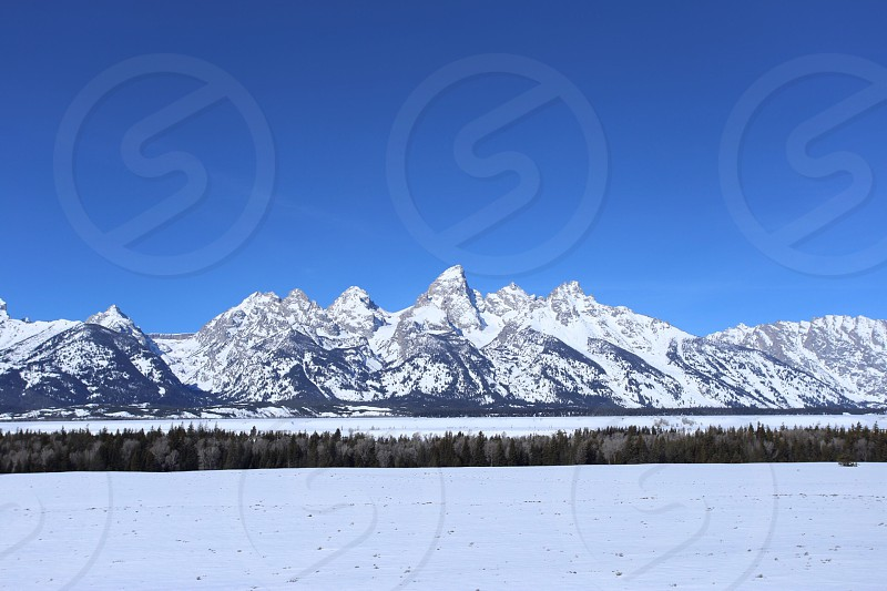 snow covered mountains under blue sunny sky photo