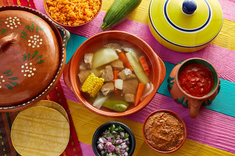 Caldo de res Mexican beef broth in table with sauces photo