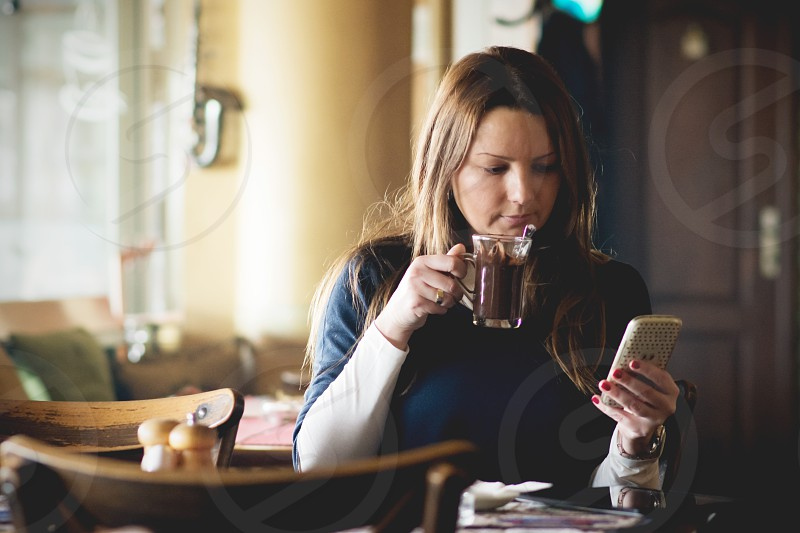 Woman enjoying hot chocolate while communicating with friends online on mobile phone in a lovely cafe photo