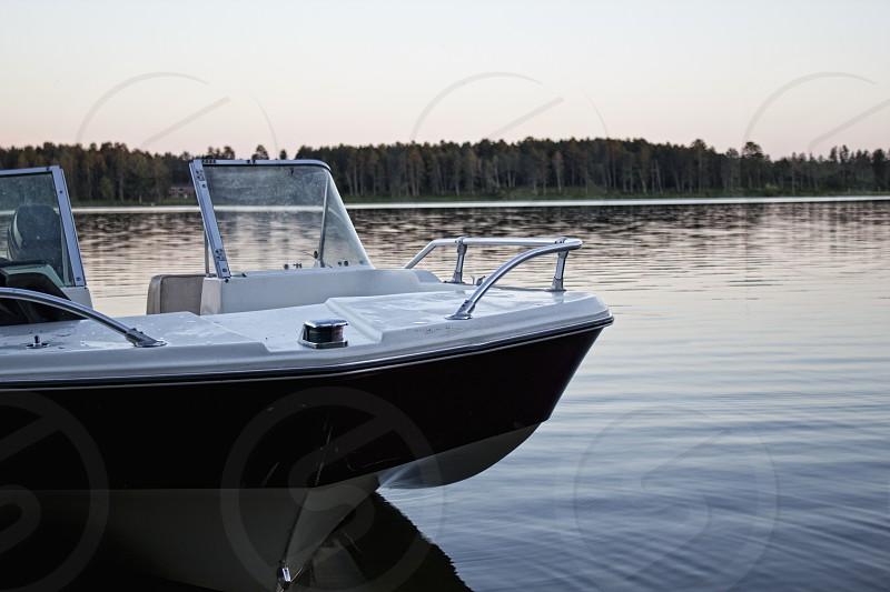 Tri-Hull boat on lake. Sunset. Calm Water.  photo