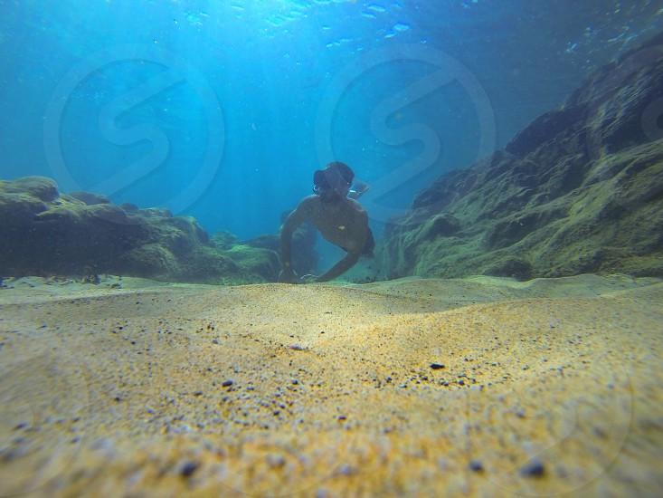 Person Swiming Under Water on Ocean Floor photo