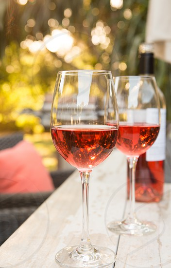 Rosé wine on wood table outdoor on a summer evening photo