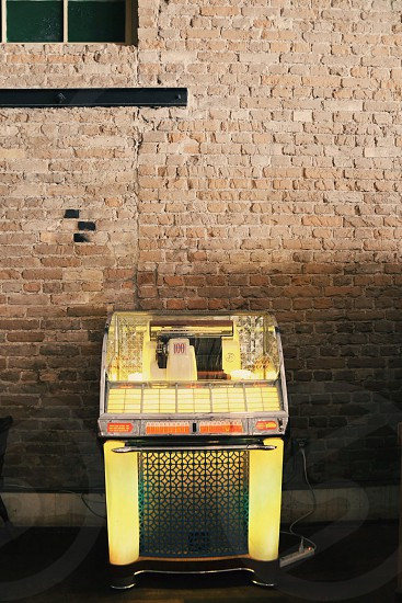 vintage yellow jukebox against red brick wall under window photo
