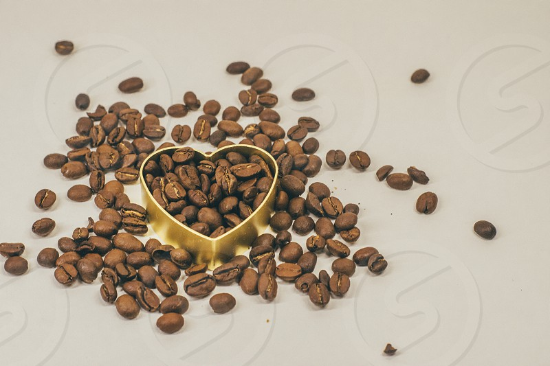 Heart symbol baking form filled with roasted coffee beans isolated on white photo