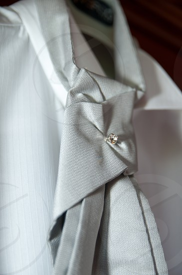 men's white button down dress shirt hanging with grey silk tie photo
