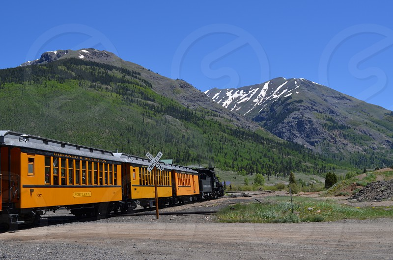 blue sky over white snow on green tree covered hillside and yellow and black train photo